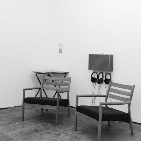 Two empty chairs. Headphones hanging on the wall.